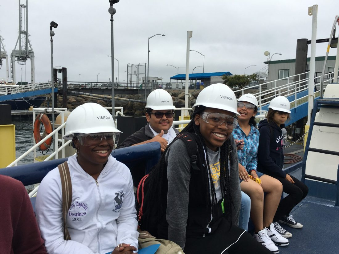 Students in hard hats smiling for a photo at California Resources Corporation's THUMS Facility Tour