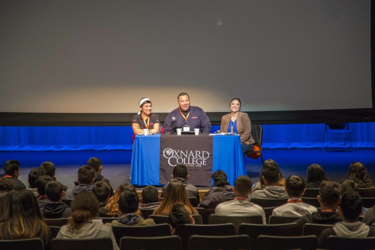 CRC employee sits on a panel in front of a crowd at an Oxnard College event.