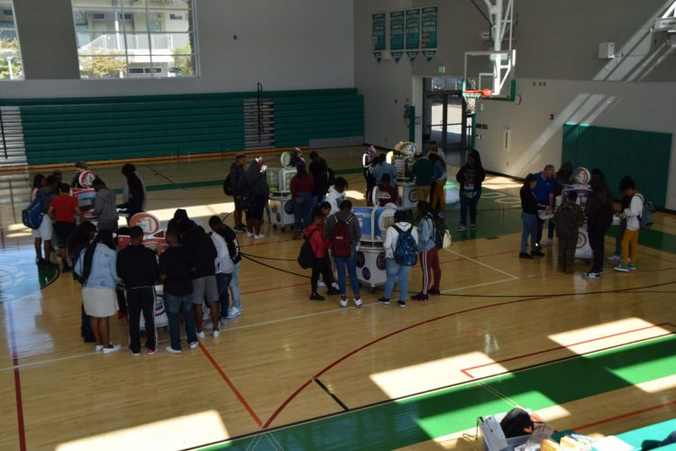 Students surround different booths at an energy event.