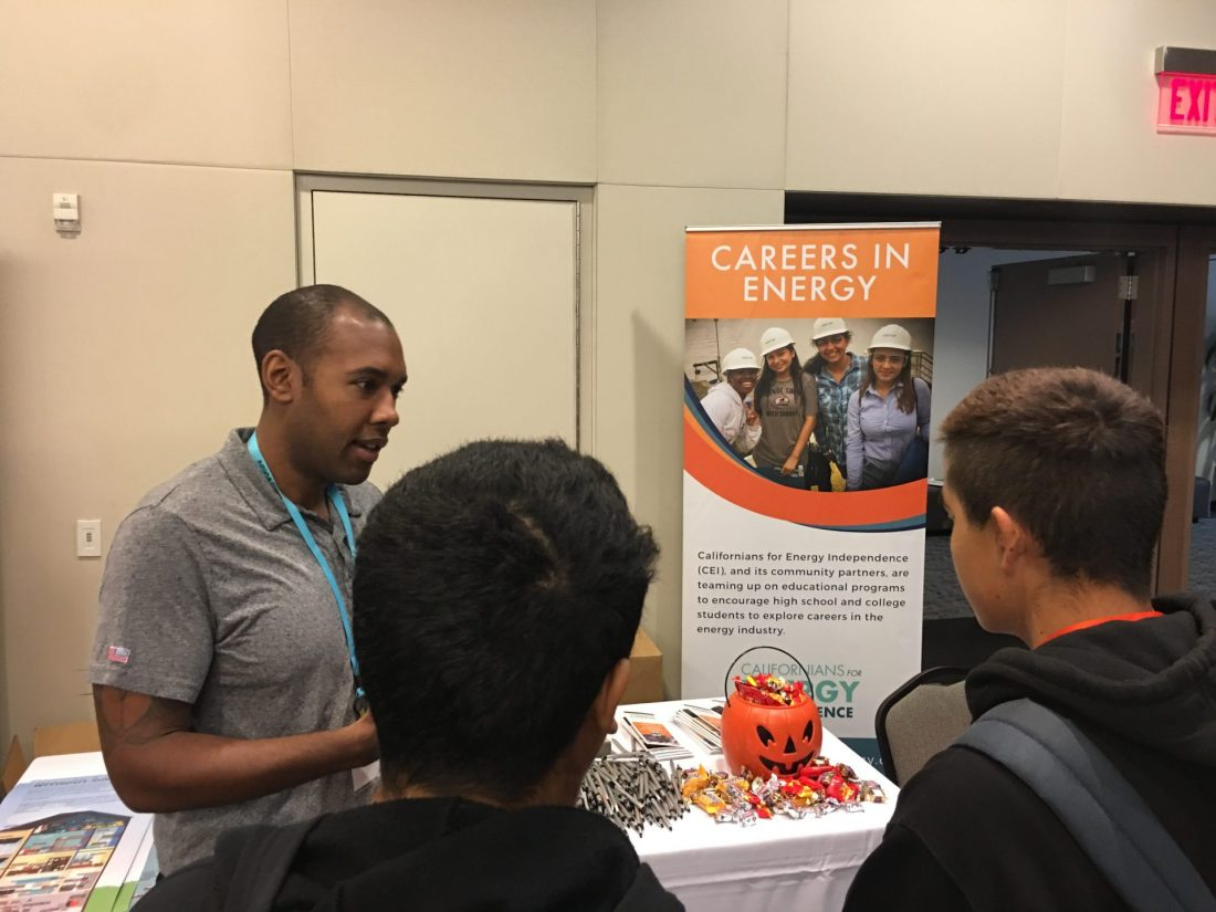 """CRC employee Mike talking with students at the Careers in Energy booth at the International Trade Education Programs """"Careers Exploration Day"""" at CSU Dominguez Hills."""
